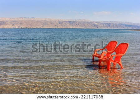 landscape with two orange chairs at the Dead Sea, north shore, Biankini Beach, Israel - stock photo
