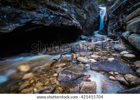 Landscape with waterfall flowing into a stony brook. - stock photo