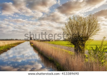 Landscape with windmill and clouds reflection in water - stock photo