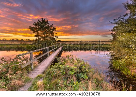 Landscape with Wooden walking bridge over river in dutch countryside near Groningen under amazing sunset during a sunday afternoon stroll. As a concept for walking over to the bright side.