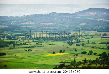 Landscape with yellow rape field, meadows, vineyards and rural houses in haze in cloudy day. A view from the medieval town Gordes on the valley. Provence, France.  - stock photo