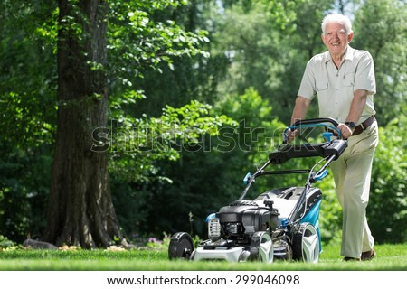 Landscape worker mowing grass in the garden