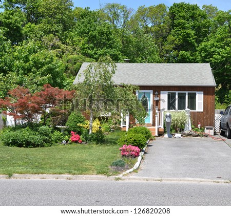 Landscaped Front Yard lawn with Blooming Azaleas Bungalow Style Home - stock photo