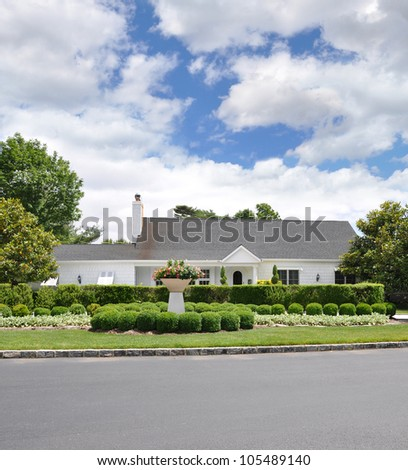 Landscaped Front Yard Suburban Ranch Style Home Blue Cloud Sky Day - stock photo