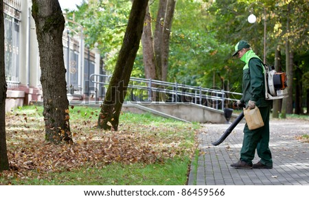 Landscaper Worker cleaning foot way in park from Dead Leaves using gas powered Leaf Blower - stock photo