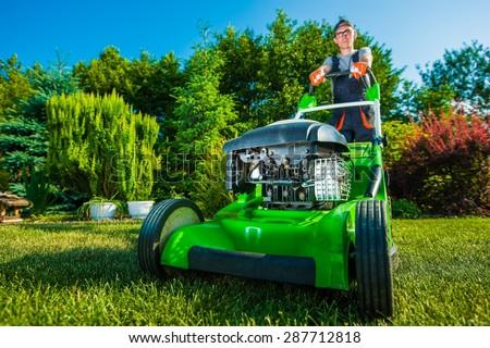 Landscaping Business. Gardener Mowing Backyard Lawn. Green Gasoline Lawn Mower - stock photo