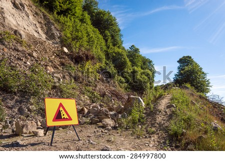 Landslide stopping a forest dirt road and warning sign.