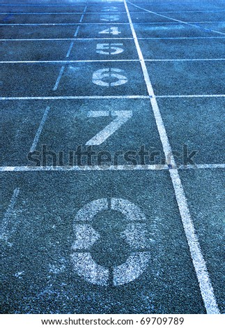 Lanes of a blue race track with numbers at high school