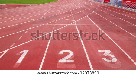 Lanes of a red race track with numbers and red seats in the stadium - stock photo