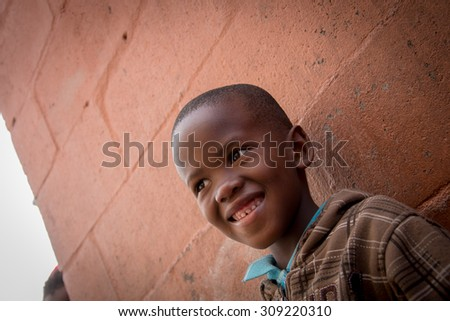 LANGA TOWNSHIP, SOUTH AFRICA - JULY 12, 2015 - A young boy poses for a photograph in a roadway in Langa, South Africa, a township located on the outskirts of Cape Town. - stock photo