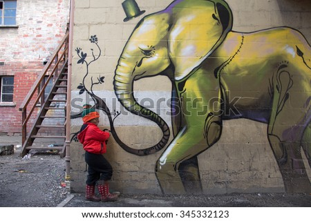 LANGA TOWNSHIP, SOUTH AFRICA - JULY 12, 2015 - A young boy poses for a photograph next to a painted building in Langa, South Africa, a township located on the outskirts of Cape Town.