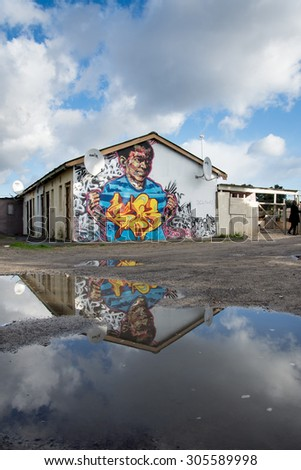 LANGA TOWNSHIP, SOUTH AFRICA - JULY 12, 2015 - Puddles in the dirt road following showers in Langa Township, located on the outskirts of Cape Town, South Africa. - stock photo