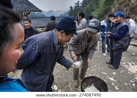 Langde Village, Guizhou, China - April 16, 2010: Rural holiday in the Chinese countryside minority Miao, boiled rice farmer lays in the hands of the guests.