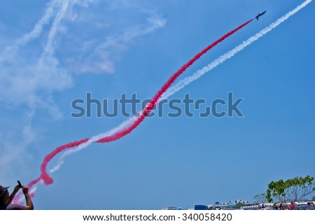 LANGKAWI, MALAYSIA - 18TH MARCH 2015; A spectator recording team Al-Fursan from U.A.E with aircraft Aermacchi MB-33 showcased their stunt during LIMA 2015 in Langkawi, Malaysia. - stock photo