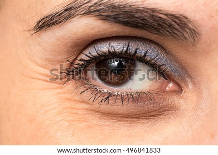 Languid gaze of adult woman with crow's feet and eye bags
