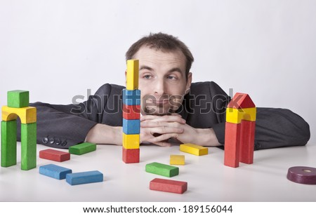 Languorous businessman plays block's toys in the office  - stock photo