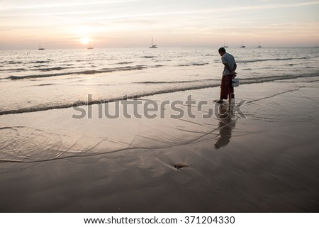 Lanta in Krabi, Thailand - February 2, 2014: The locals on the beach looking for molluscs, during low tide at sunset sky background.