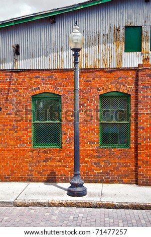 lantern and facade of old brick house - stock photo