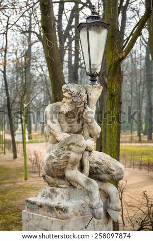 Lantern decorated by sculpture of satyr in Lazienki Park (Royal Baths Park) of Warsaw, Poland - stock photo