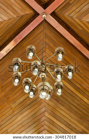 Lantern hanging from a giant wooden arch. below angle. - stock photo