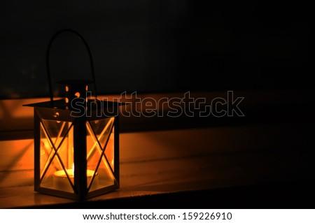 Lantern in a dark window - stock photo