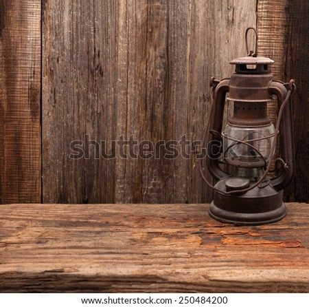lantern lamp old wooden table wall background - stock photo