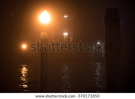 Lantern on a wooden pole in Venice at night. View of a dim lit Venice channel in a night fog with shallow depth of field - stock photo