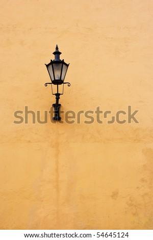 Lantern on a yellow wall - stock photo