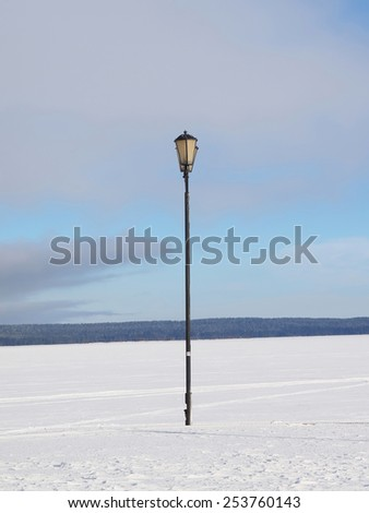 Lantern on the bank of lake in the winter