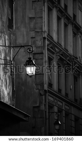 Lantern on the building wall. Paris, France. Sepia. Aged photo. Sunlight is highlighting the lantern attached to the wall and the rest of the street is in the shadow.