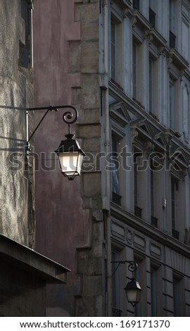 Lantern on the building wall. Paris, France. Sunlight is highlighting the lantern attached to the wall and the rest of the street is in the shadow.