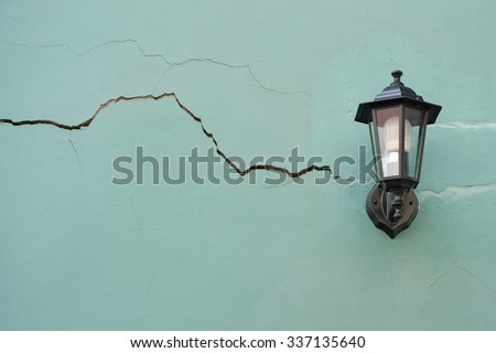 Lantern on the cracked wall. The facade of the building. - stock photo
