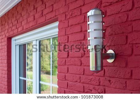 Lantern outside the house next to a window - stock photo