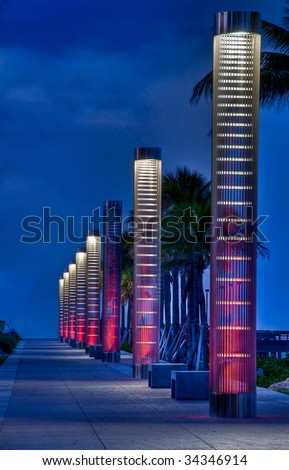 Lanterns illuminating path to the beach at night in South Pointe Park, Miami Beach. - stock photo