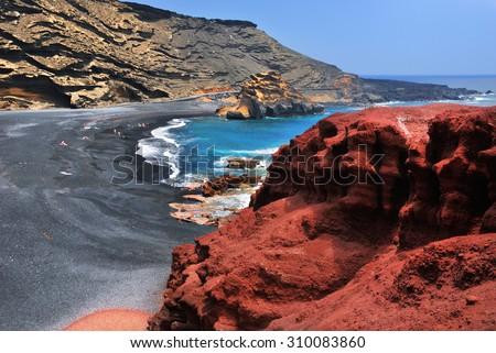 Lanzarote, black sandy beach in gulf of El Golfo, Atlantic ocean near Lago de los Clicos in Canary Islands  - stock photo