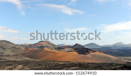 Lanzarote, Canary Islands, Spain. A crater and volcanic mountains in Timanfaya Natural Park, with clouds in the sky.