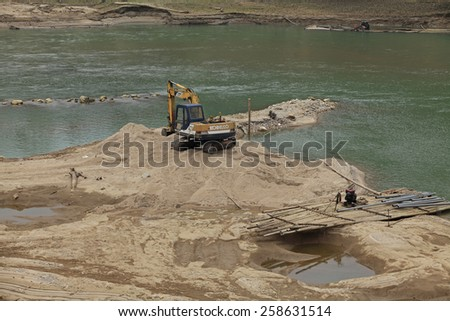 LAO CAI, VIETNAM - FEB 10, 2015: Machines digging into Chay river to mine sand, that resulting in many uncontrolled impacts of nature as types of climate change.  - stock photo