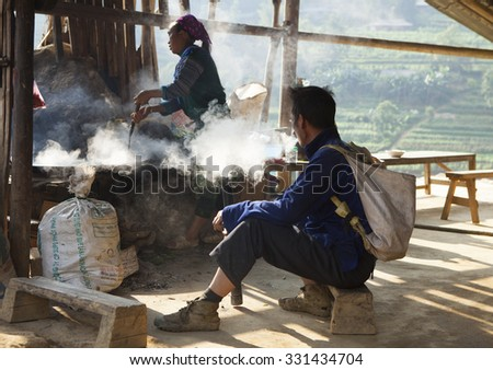Lao Cai, Vietnam - Oct 17, 2015: Asian minority man smoking beside a kitchen with a woman cooking traditional hotpot of horse meat in time of weekly flea market taking place in Simacai district. - stock photo