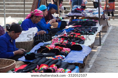 Lao Cai, Vietnam - Oct 17, 2015: Asian senior tailors sewing and selling colorful traditional textile products at Bac Ha weekly flea market, north west of Vietnam.