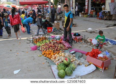 LAOMENG - DECEMBER 16: Fruit trader waits for customers at a market in Lao Meng, China on December 16, 2012. People from 13 tribes/ethnic groups from China and Laos congregate here to trade daily.
