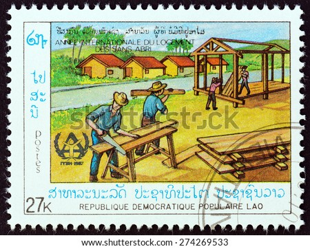 "LAOS - CIRCA 1987: A stamp printed in Laos from the ""International Year of Shelter for the Homeless "" issue shows building wooden house, circa 1987."