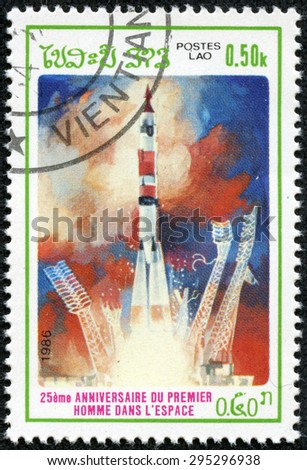 "LAOS - CIRCA 1986: A stamp printed in Laos from the ""25th anniversary of First Man in Space "" issue shows Rocket launch at Baikanur Space Centre, circa 1986. - stock photo"