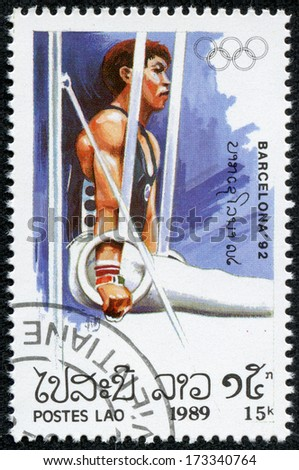 LAOS - CIRCA 1989: A stamp printed in Laos shows gymnast on the rings, series Olympic Games in Barcelona 1992, circa 1989 - stock photo