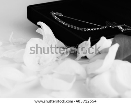 Lapel pin box , blurred rose petals on white background / Black and white