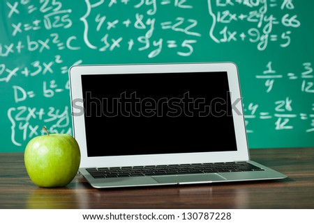 Laptop and apple on the desk in front of blackboard - stock photo