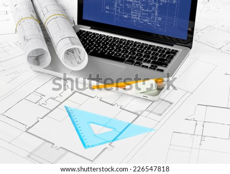 Laptop and blueprints on working table - stock photo