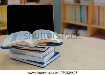 Laptop and book on a desk in library - stock photo