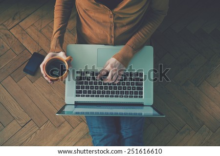 Laptop and coffee cup in girl's hands sitting on a wooden floor - stock photo