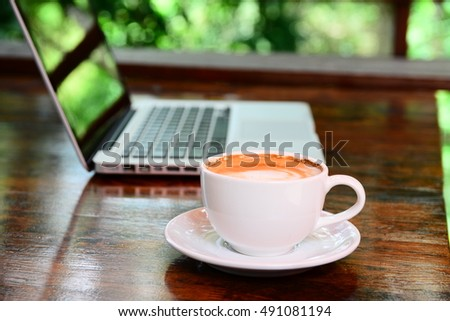 Laptop and coffee cup on old wooden table with blurred background