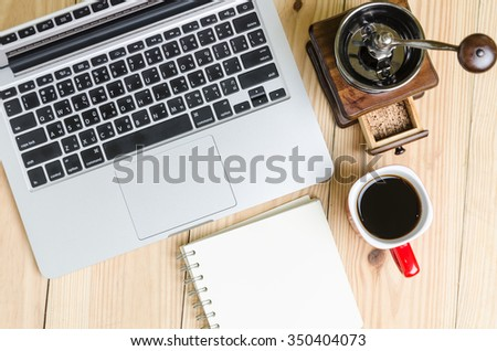 Laptop and coffee cup on wood table. View from above